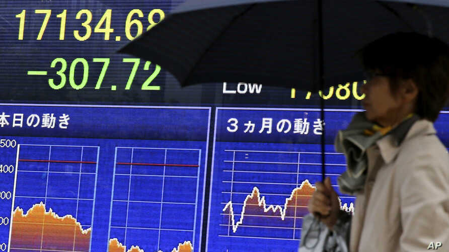 People walk past an electronic board showing the Nikkei stock index in Tokyo, Nov. 2, 2016.
