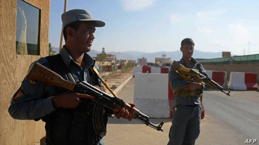 Afghan policemen keep watch at the scene following a suicide attack in Mazar-i-sharif, Oct. 12, 2014.