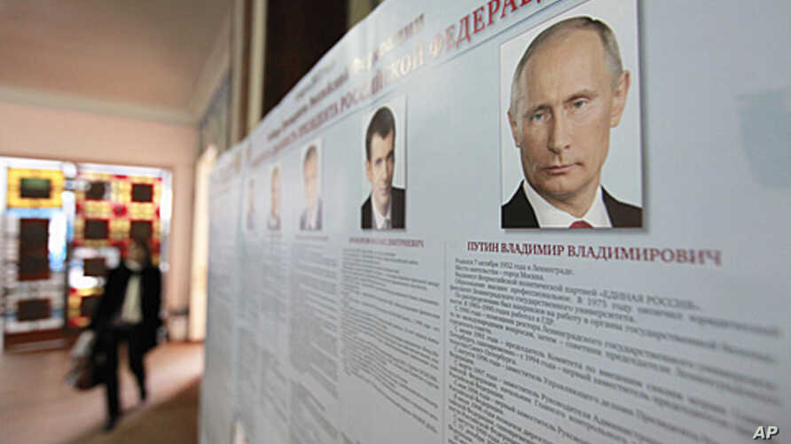 A board with the profiles of various presidential candidates, amongst them Russia's current Prime Minister Vladimir Putin, is on display during the preparations for the upcoming presidential elections at a polling station in the southern Russian city