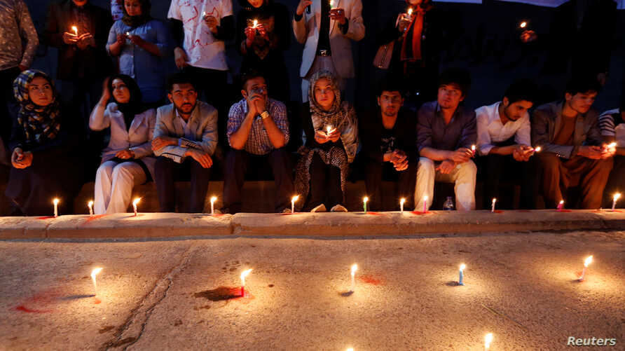 People hold lit candles for the victims of an explosion in Kabul, Afghanistan, June 1, 2017.
