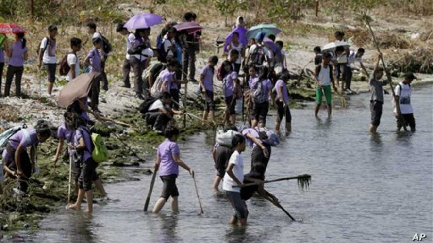 Students join other environmental activists in a coastal clean-up along the shores of Freedom Island to mark World Earth Day Wednesday, April 22, 2015 at suburban Las Pinas, south of Manila, Philippines. The Freedom Island, which is home to about 80