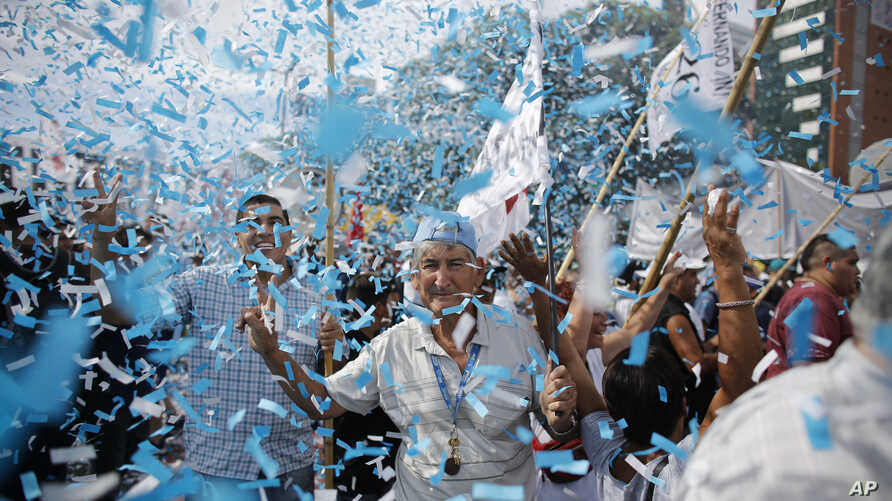 Confetti representing colors of the Argentine flag rain on demonstrators during a labor march in Buenos Aires, Argentina, March 7, 2017.