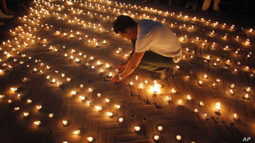Nepalese people light candles in memory of those who died in last year's devastating earthquake in Basantapur Durbar Square in Kathmandu, Nepal, April 24, 2016.