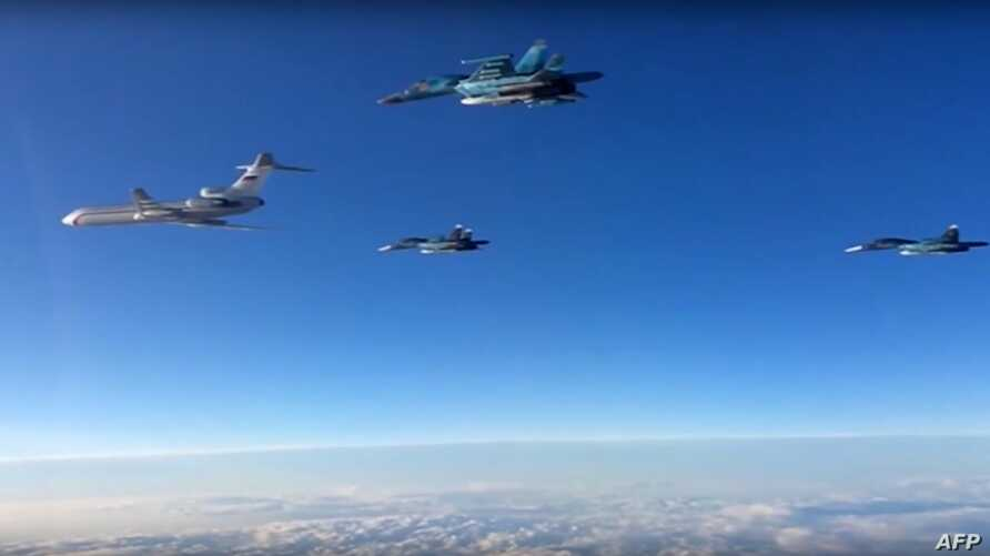 A video grab made on March 15, 2016, shows an image taken from a footage made available on the Russian Defence Ministry's official website on March 15, 2016, reportedly showing Russian Su-34 bombers and a Tupolev Tu-154 transport plane (L) flying abo