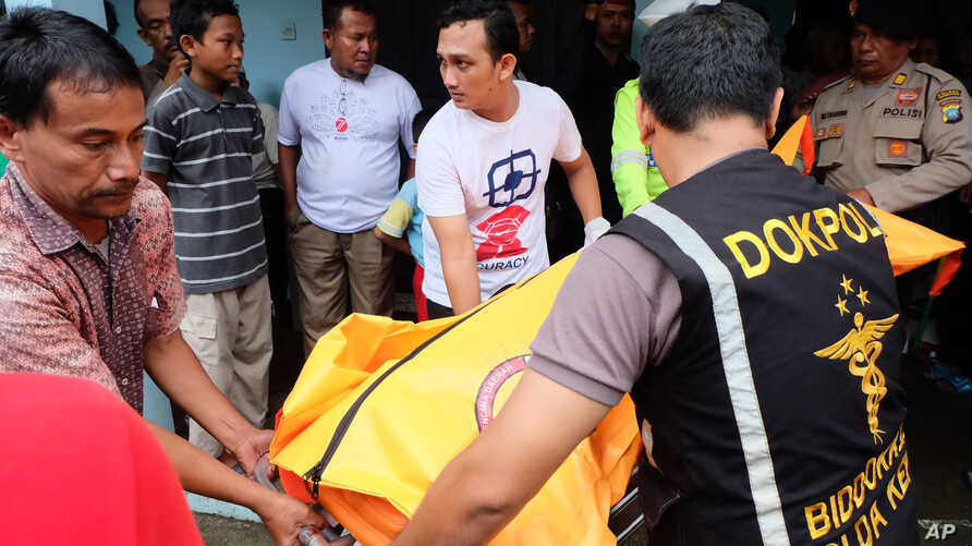Indonesian police carry a body bag containing a victim of a capsized boat, at a hospital in Tanjungpinang, Bintan island, Aug. 21, 2016.