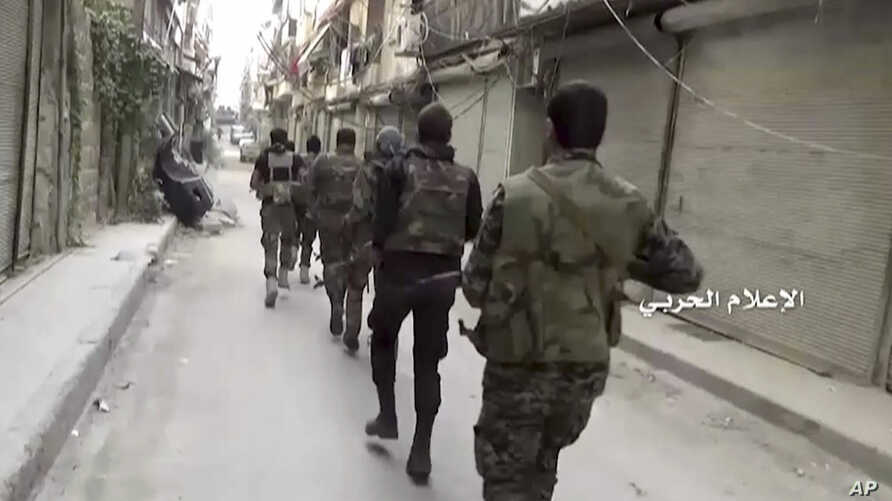 In this still image taken from video provided by the Syrian government-controlled Syrian Central Military Media, government troops patrol inside the Bustan Al-Basha neighborhood of Aleppo, Syria.