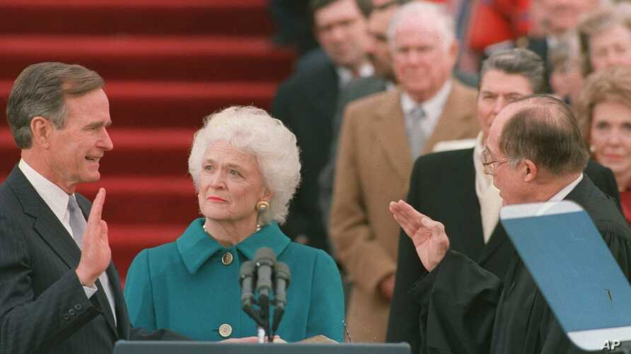 FILE - President George H.W. Bush raises his right hand as he is sworn into office as the 41st president of the United States by Chief Justice William Rehnquist outside the west front of the Capitol as first lady Barbara Bush holds the bible for her