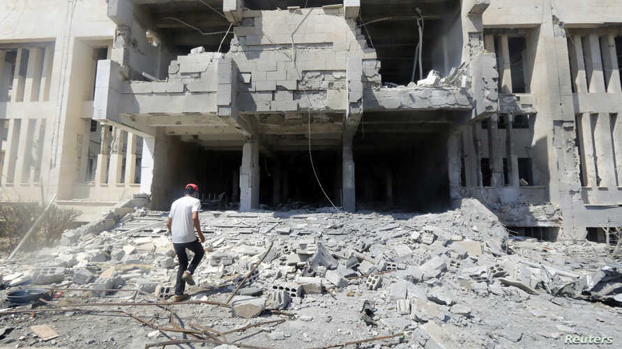 A man inspects damage at the entrance of the National Hospital of al-Tabqa, caused by what activists said was an airstrike by forces of Syria's President Bashar Al-Assad on the hospital, beside al-Tabqa military base, west of Raqqa, Aug. 23, 2014.