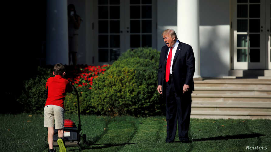 U.S. President Donald Trump welcomes 11-year-old Frank Giaccio as he cuts the Rose Garden grass at the White House in Washington, Sept. 15, 2017.