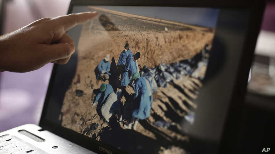 FILE _ Sirwan Jalal, Director of Mass Graves for the Kurdish Regional Government, points to an image of the site of a mass grave during an interview with the Associated Press in Irbil, northern Iraq.