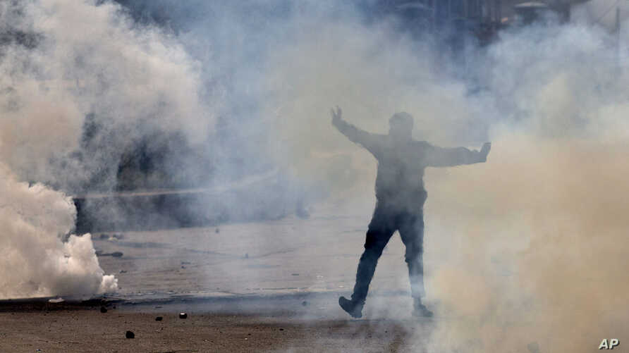 FILE - A Kashmiri Muslim protester shouts slogans amid tear gas during a protest in Srinagar, Indian-controlled Kashmir, Oct. 30, 2015. Kashmiris had gathered to protest the killing of Abu Qasim, a Pakistani national and operations chief of the Lashk