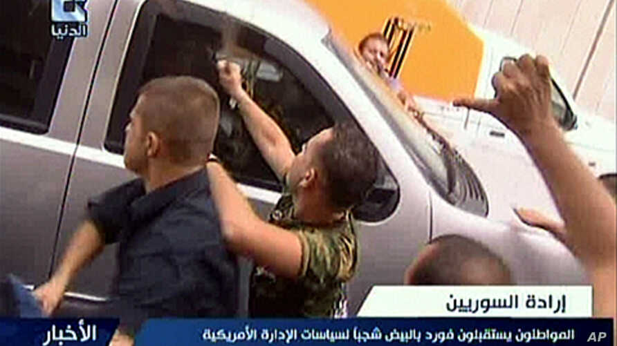 A still image grab taken from the Syrian 'Addounia' pro-government television channel shows pro-regime Syrians attacking a US embassy vehicle in Damascus, September 29, 2011.