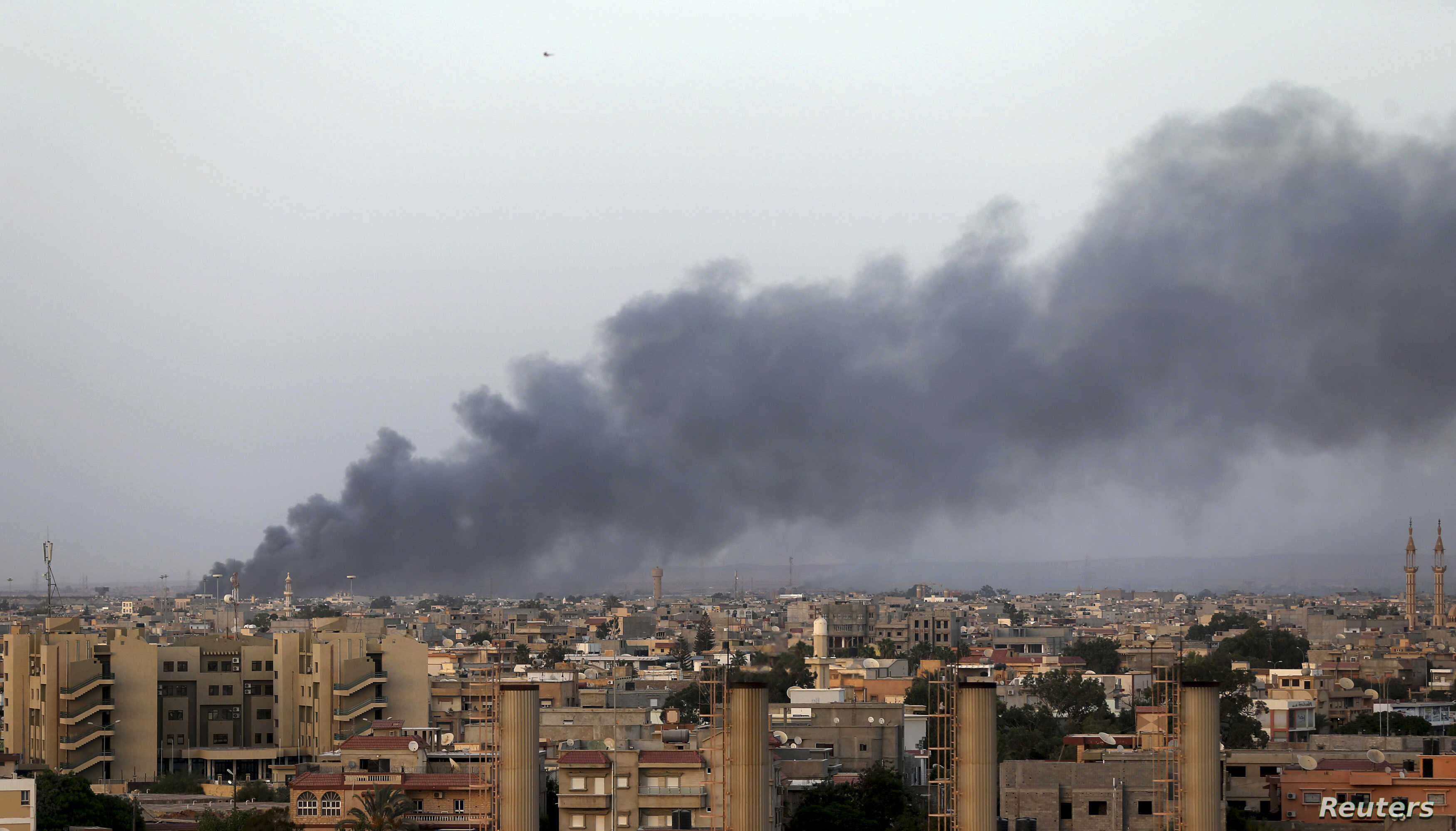 Plumes of black smoke can be seen after clashes between the Benghazi Revolutionaries Shura Council and fighters of renegade general Khalifa Haftar, as they each attempt to seize control of the airport from the council in Benghazi, Libya, Aug. 23, 201