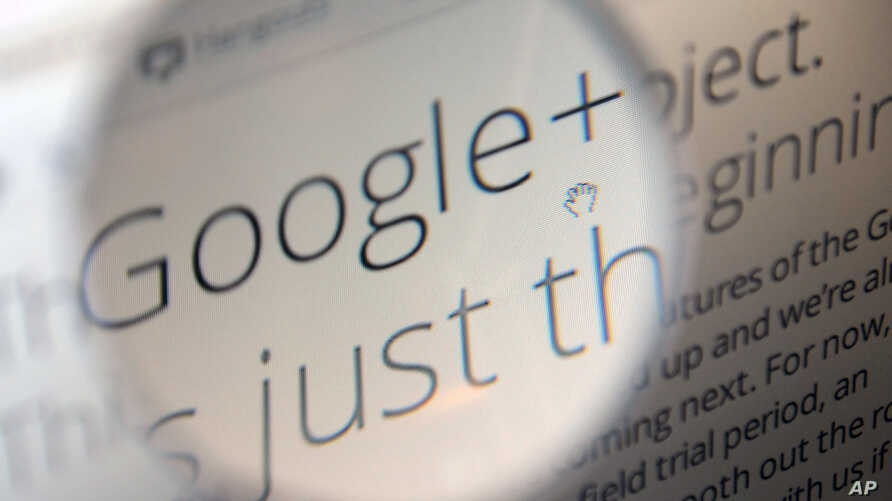 A computer monitor in Berlin displays information about Google+ service, seen through a magnifying glass, June 29, 2011