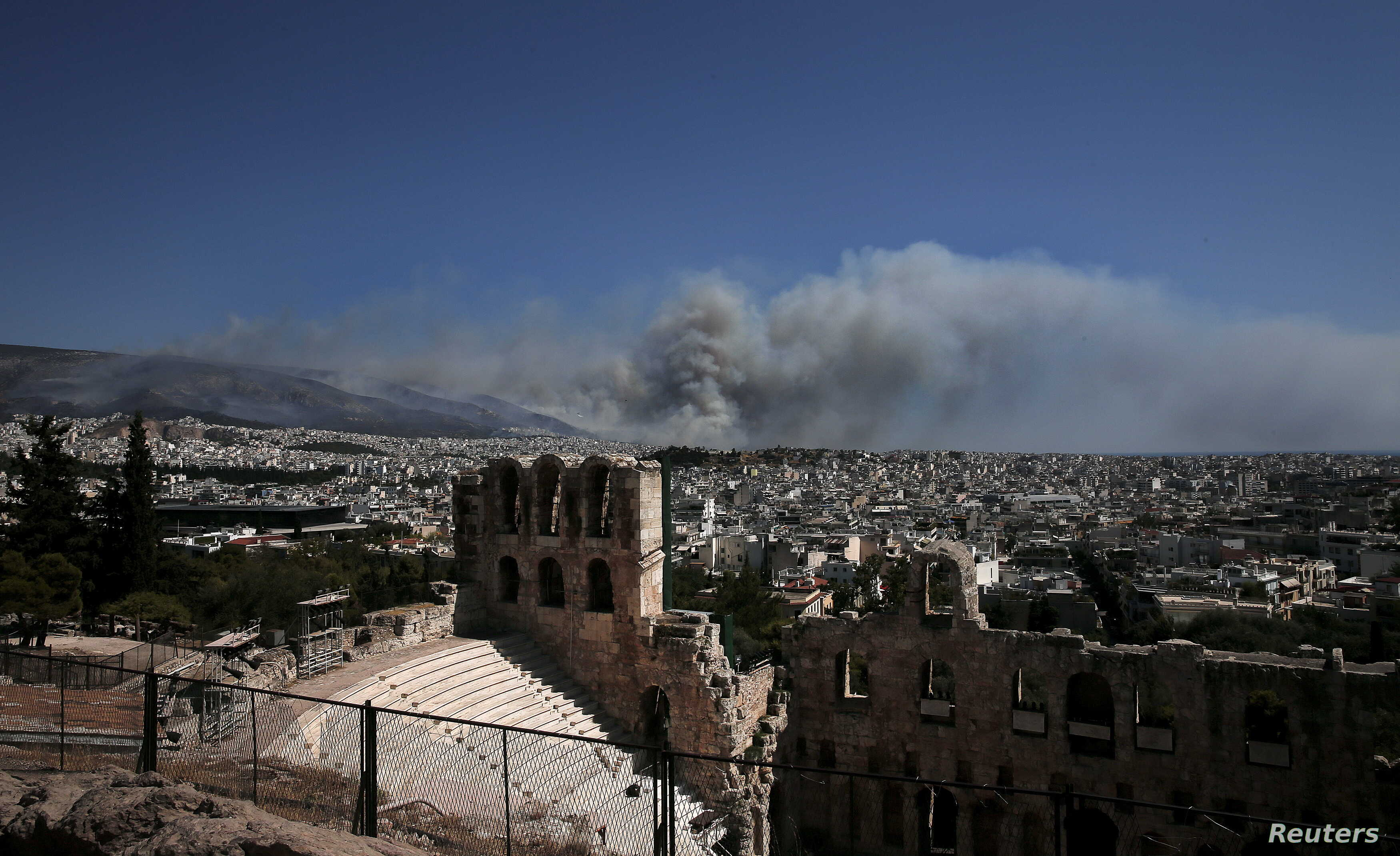A view of the Herodes Atticus theater as smoke from a raging wildfire rises in Athens, Greece, July 17, 2015.