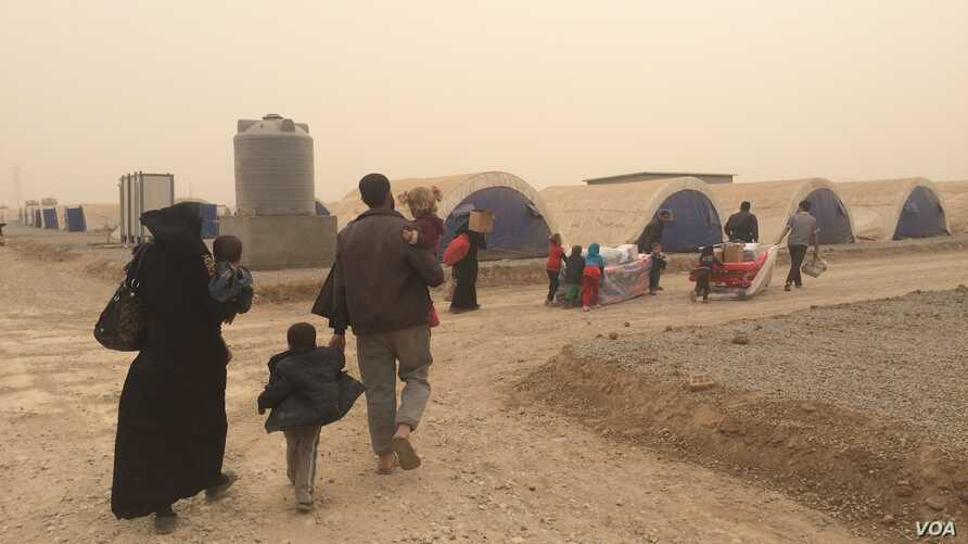 On the day Abu Youseff and his four children arrived at the Khazir camp, a sand storm hit, forcing the exhausted refugees to race into tents, Iraqi Kurdistan, Nov. 1, 2016. (H.Murdock/VOA)