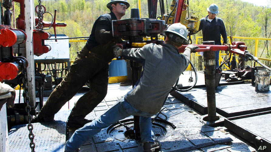 FILE - Workers move a section of well casing into place at a Chesapeake Energy natural gas well site near Burlington, Pennsylvania, April 23, 2010.