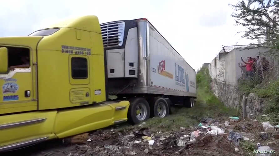 A truck leaves with an abandoned trailer full of bodies that has been parked in Tlajomulco de Zuniga, Jalisco, Mexico ,Sept. 15, 2018 in this image taken from video.