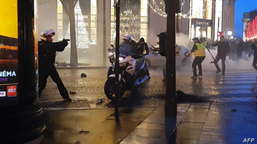 """This frame from a video taken Dec. 22, 2018, on the Champs-Elysees in Paris shows a police biker, left, drawing his firearm as he and other police bikers are assaulted by protesters, during the sixth consecutive Saturday of mobilization of the """"yello"""