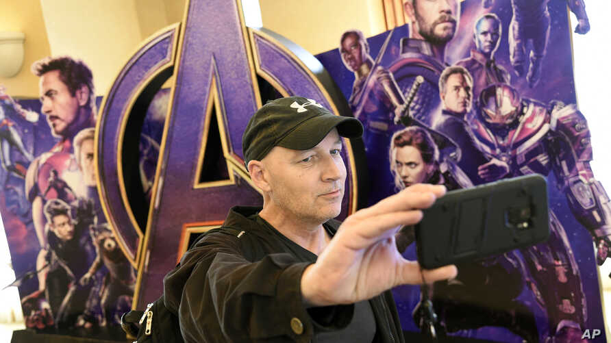 "CinemaCon attendee Luis Saint Amant, of Argentina, takes a selfie in front of an advertisement for the upcoming film ""Avengers: Endgame,"" on the first day of CinemaCon 2019, the official convention of the National Association of Theatre Owners (NATO)"