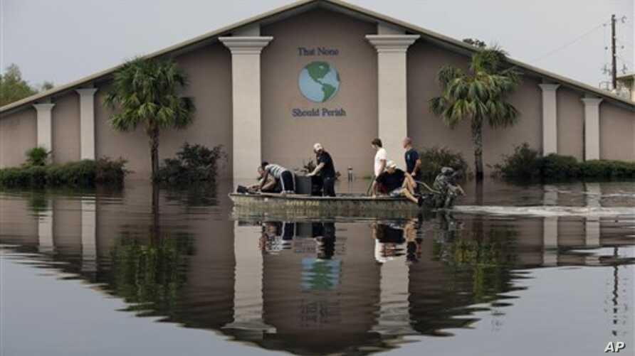 Volunteers use a boat to recover sound equipment from a flooded church in the aftermath of Isaac, in Reserve, Louisiana, August 31, 2012.