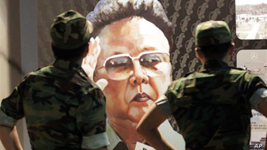 South Korean soldiers look at a poster of North Korean leader Kim Jong Il, painted by North Korean defector Sun Moo, at the Korea War Memorial Museum in Seoul, South Korea, Tuesday, Sept. 7, 2010.