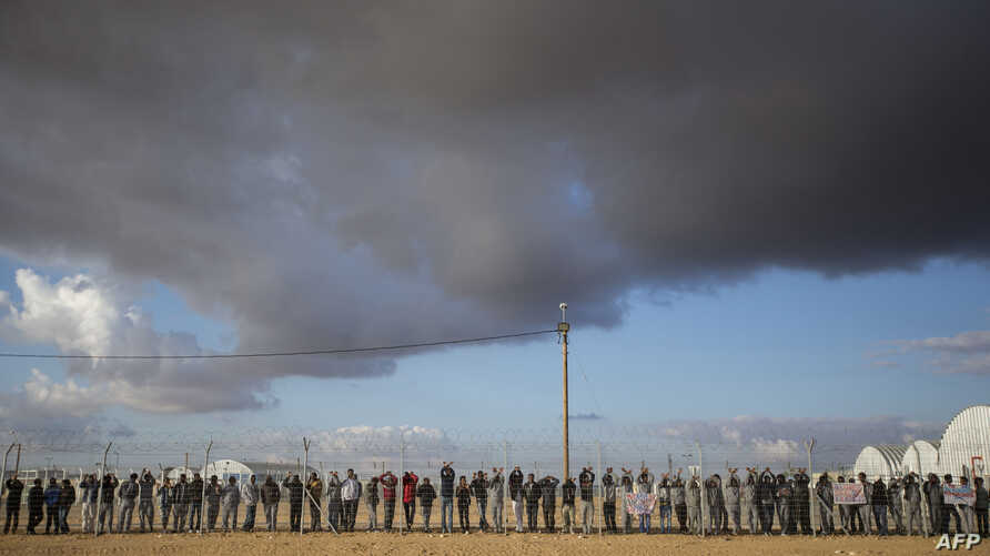 FILE - African asylum seekers, who entered Israel illegally via Egypt, lean at the fence of the Holot detention center in Israel's southern Negev Desert, on Feb. 17, 2014 as they join other migrants who came to protest outside the detention facility.