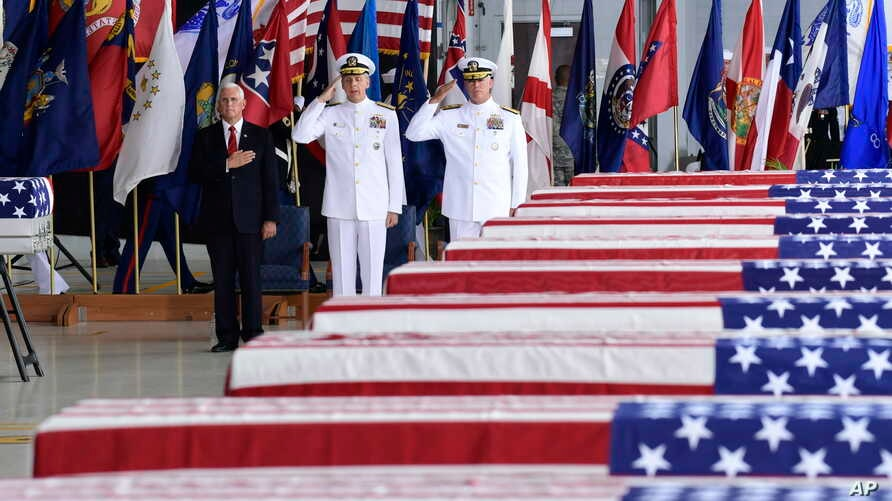 Vice President Mike Pence, left, Commander of U.S. Indo-Pacific Command Adm. Phil Davidson, center, and Rear Adm. Jon Kreitz, deputy director of the POW/MIA Accounting Agency, attend at a ceremony marking the arrival of the remains believed to be of