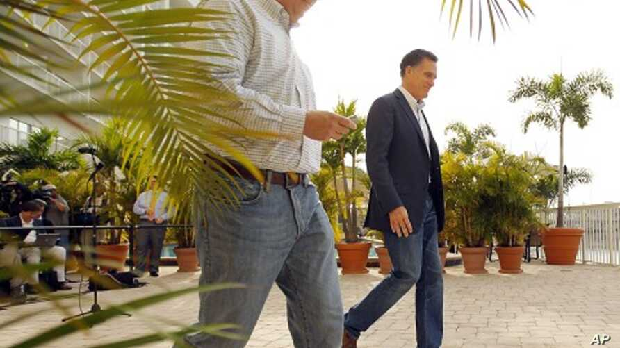 Republican presidential candidate and former Massachusetts Governor Mitt Romney and traveling press secretary Rick Gorka walk away after speaking to reporters in Tampa, January 23, 2012