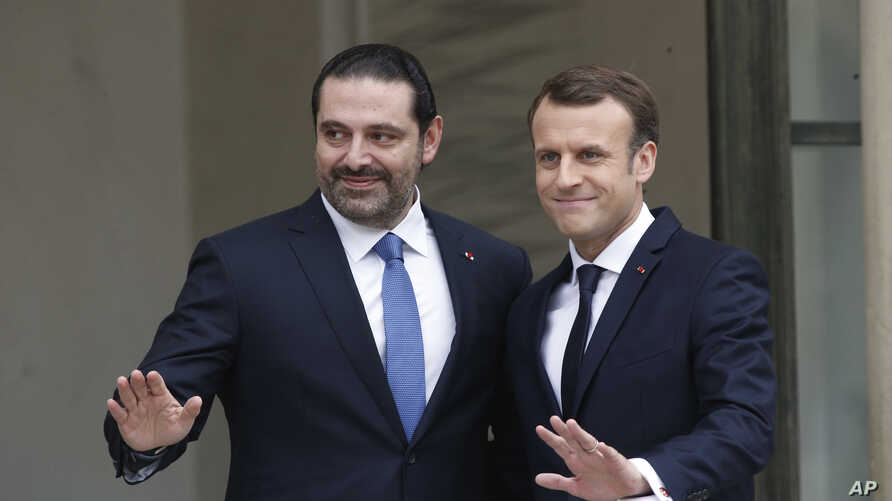 French President Emmanuel Macron, right, poses for photographers with Lebanon's Prime Minister Saad Hariri prior to their meeting at the Elysee Palace in Paris, Saturday, Nov. 18, 2017.