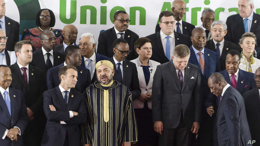 French President Emmanuel Macron, center left, speaks with Morocco's King Mohammed VI, center right, during a group photo at an EU Africa summit in Abidjan, Ivory Coast on Wednesday, Nov. 29, 2017.
