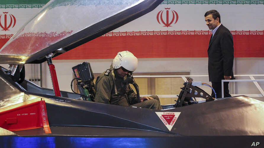 Iranian President Mahmoud Ahmadinejad, center, listens to an unidentified pilot during a ceremony to unveil Iran's newest fighter jet, Qaher-313, or Dominant-313,which officials claim can evade radar, in Tehran, Iran, February 2, 2013.