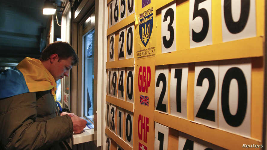 FILE - A man exchanges money at a currency exchange office in Kyiv April 10, 2014.