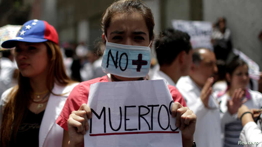 """A woman wears a mask and a banner that read """"No more deaths"""" as she takes part in a rally of workers of the health sector against President Nicolas Maduro's government in Caracas, Venezuela May 17, 2017."""