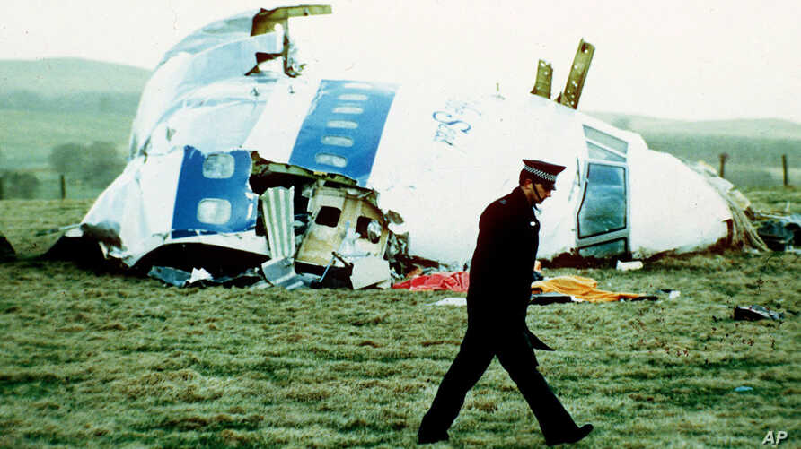 A police officer walks by the nose of Pan Am flight 103 in a field near the town of Lockerbie, Scotland where it lay after a bomb aboard exploded on Dec. 21, 1988.