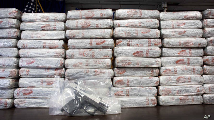 FILE - A firearm and 154 pounds of heroin worth at least $50 million are displayed at a Drug Enforcement Administration news conference, in New York, May 19, 2015. An annual DEA survey released Nov. 4, 2015, says heroin and drug overdoses have reache