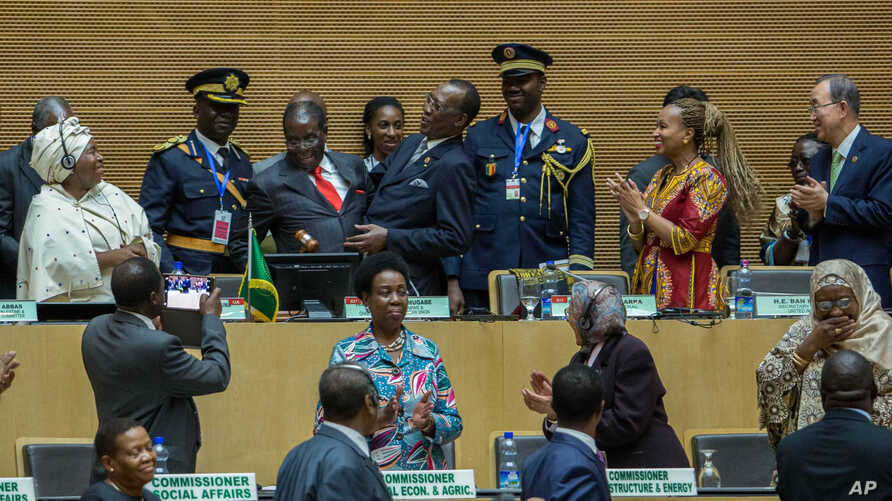 African Union chairman Chadian President Idriss Deby, fourth left, receives the instruments of office from his predecessor Zimbabwean President, Robert Mugabe, third left in red tie, as African Union Commission Chairperson Nkosazana Dlamini Zuma, lef