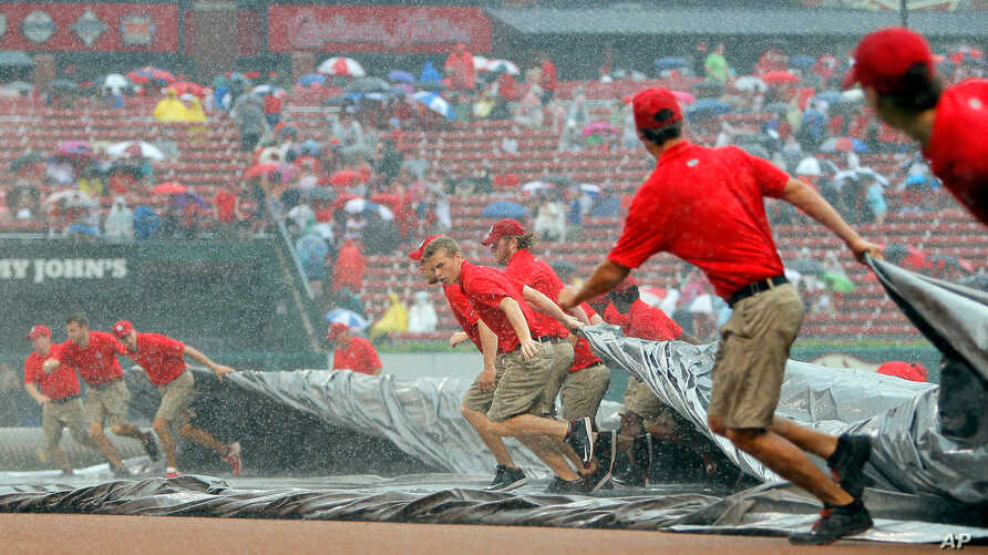 Members of the St. Louis Cardinals grounds crew pull the tarp over the infield as it rains during the first inning of a baseball game against the Minnesota Twins, June 16, 2015, in St. Louis.