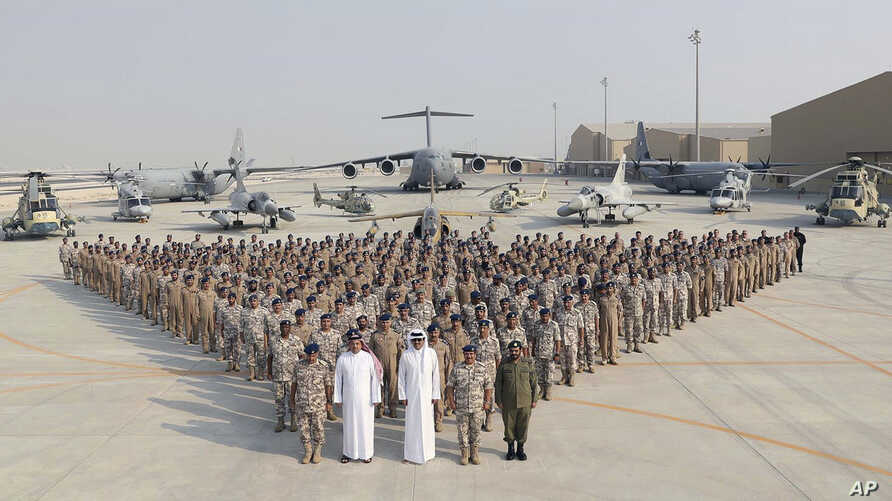 In this Sept. 11, 2017 photo released by Qatar News Agency, the Qatari Emir Sheikh Tamim bin Hamad Al Thani, centre front, poses for a photo with Emiri Air Force at al-Udeid Air Base in Doha, Qatar.