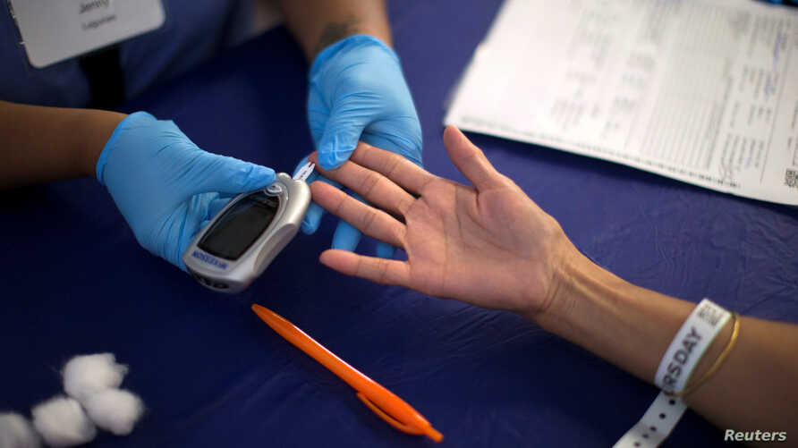 FILE - A person receives a test for diabetes at a free medical clinic in Los Angeles, California, Sept. 11, 2014. According to a new study, the drugs that can help treat autoimmune diseases like diabetes can also help treat depression.