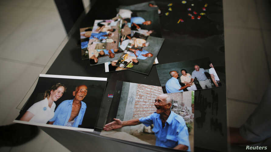 Pictures of Liu Guolian's father Liu Qian, who was a forced labourer by Mitsui Mining to work in their mines in Fukuoka of Japan, are seen on a table during an interview with Reuters on the outskirts of Beijing, April 28, 2014.