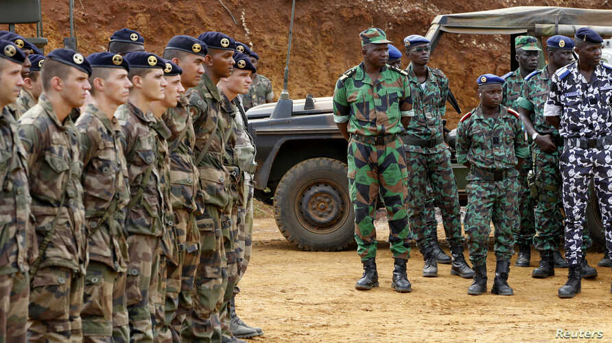 French soldiers stand near Ivorian soldiers in Toumodi, during a military training ahead of the departure of Ivorian soldiers for Mali, Apr. 6, 2013.