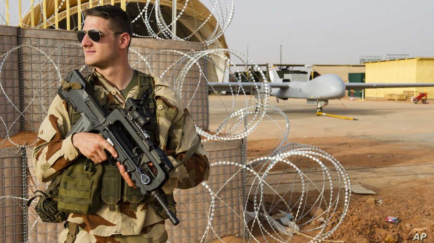 FILE - A French air force soldier on guard near a Hartford drone, at the Niamey military base, in Niger.