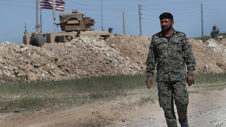 FILE - A U.S-backed Syrian Manbij Military Council soldier passes a U.S. position near the tense front line with Turkish-backed fighters, in Manbij, north Syria, April 4, 2018.