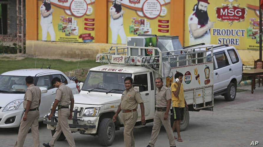Indian policemen walk in front of a store belonging to Dera Sacha Sauda sect chief Gurmeet Ram Rahim Singh after it was sealed by authorities, near Sonipat, India, Aug. 26, 2017. Security forces on Saturday patrolled the streets of the north Indian s...