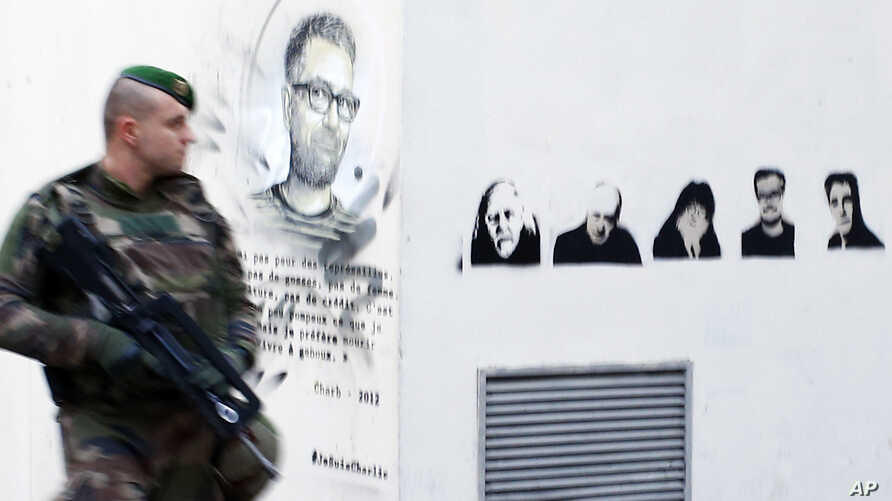 A french soldier patrols next to a painting of killed cartoonists, Charb at left, and at right, Honore, Wolinski, Cabu, Charb and Tignous outside satirical newspaper Charlie Hebdo former office, one year after the attacks on it, in Paris, France, Jan...