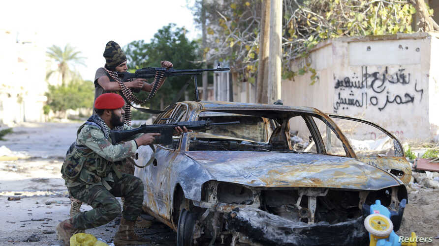 Pro-government Libyan forces aim their weapons during clashes with the Shura Council of Libyan Revolutionaries, an alliance of former anti-Gadhafi rebels, who have joined forces with the Islamist group Ansar al-Sharia, in Benghazi, December 28, 2014.