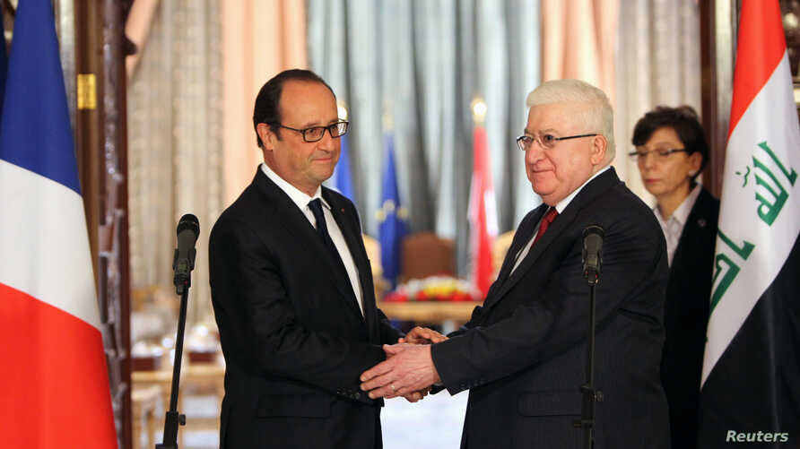 French President Francois Hollande shakes hands with Iraqi President Fuad Masum (R) during a news conference in Baghdad, Sept. 12, 2014.