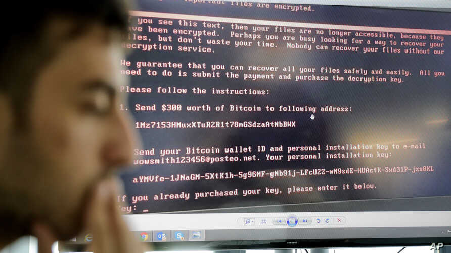 Razvan Muresan, a Bitdefender public relations specialist, is backdropped by a screenshot of the message displayed on computers affected by the latest cyberattack, in Bucharest, Romania, June 28, 2017.  A new, highly virulent strain of malicious rans