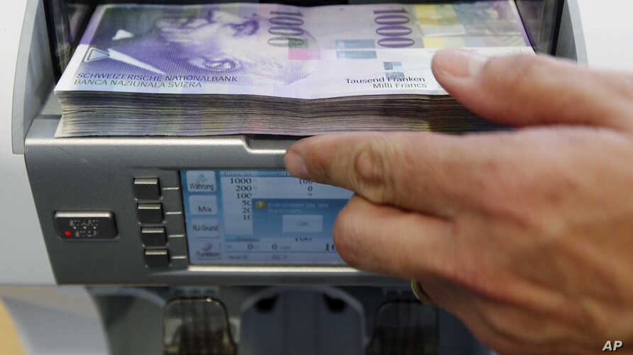 A bank clerk places1000 Swiss franc banknotes in a money counter in a Bank in Bern (file photo)